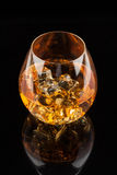 Glass of Whiskey. A glass of whiskey on the rocks  on black background Stock Images