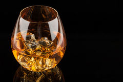 Glass of Whiskey. A glass of whiskey on the rocks  on black background Stock Image