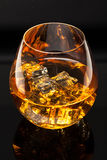 Glass of Whiskey. A glass of whiskey on the rocks  on black background Stock Photography