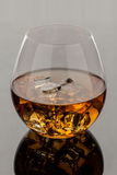 Glass of Whiskey. A glass of whiskey on the rocks  on gray background Stock Image