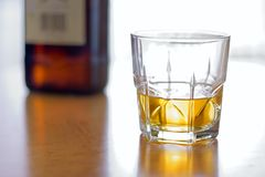Glass of whiskey. Glass of yellow whiskey and brown bottle on the table Stock Photos
