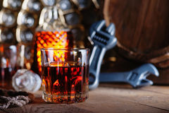 Glass of whiskey with adjustable wrenches and wooden barrel. Glass of whiskey with silver adjustable wrenches and wooden barrel Stock Photos
