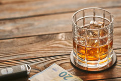 Glass of whiskey or alcohol drink with ice cubes and car key. Drink and drive concept. Royalty Free Stock Image
