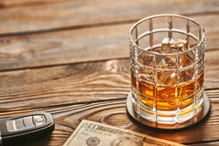 Glass of whiskey or alcohol drink with ice cubes and car key. Drink and drive concept. Royalty Free Stock Images