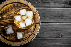 Glass of whiskey on the barrel. On wooden background royalty free stock images