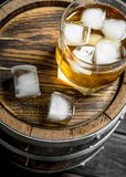 Glass of whiskey on the barrel. On wooden background royalty free stock photography
