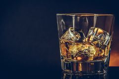 Glass of whiskey on black background with reflection, warm atmosphere Stock Image