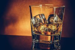 Glass of whiskey on black table with reflection and gold background, warm atmosphere Stock Photos