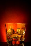 Glass of whiskey on black table with reflection, red tint atmosphere Royalty Free Stock Photo