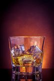 Glass of whiskey on black table with reflection, violet light tint atmosphere Stock Photo