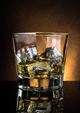 Glass of whiskey on black table with reflection, warm atmosphere dark light Royalty Free Stock Photos