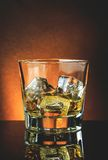 Glass of whiskey on black table with reflection, warm atmosphere Stock Photos