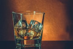Glass of whiskey on black table with reflection, warm atmosphere Royalty Free Stock Images