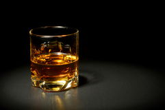 Glass of whiskey on black table Stock Photography