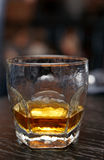 Glass of whiskey on black wooden surface Stock Photos