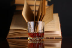 Glass of whiskey and books Stock Images