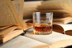 Glass of whiskey on books Royalty Free Stock Images