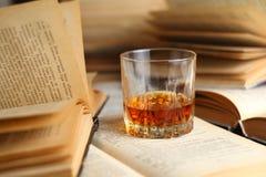 Glass of whiskey on books Stock Photos