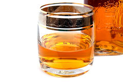 Glass of whiskey with a bottle. Half glass of whiskey with a bottle white isolated Stock Image