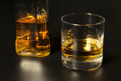 A glass of whiskey and bottle on dark table Stock Image