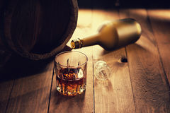 Glass of whiskey, bottle and wooden barrel Stock Image