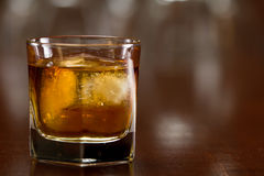 Glass of whiskey. Bourbon whiskey served with ice on a out of focus busy bar Royalty Free Stock Photography