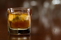 Glass of whiskey. Bourbon whiskey served with ice on a out of focus busy bar Stock Photo