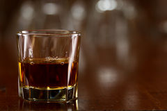 Glass of whiskey. Bourbon whiskey served neat on a out of focus busy bar Royalty Free Stock Images