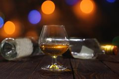 Glass of whiskey or brandy and empty bottles on wooden table on bright glowing background royalty free stock photos