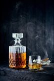 Glass of whiskey and carafe. On a black wooden table Royalty Free Stock Photos
