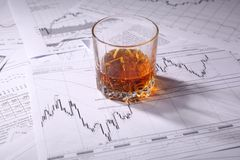 Glass of whiskey on charts Royalty Free Stock Photo
