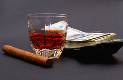 Glass with whiskey, cigar and a batch of money upon a brown wallet on the dark background Royalty Free Stock Photos