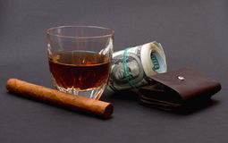 Glass with whiskey, cigar and a roll of money upon a brown wallet on the dark background Royalty Free Stock Image
