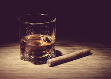 Glass of whiskey and a cigar on wooden table Stock Image