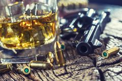 Glass of whiskey cognac or bourbon with revolver and bullets on stock photography