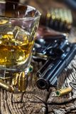 Glass of whiskey cognac or bourbon with revolver and bullets on stock photos