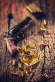 Glass of whiskey cognac or bourbon with revolver and bullets on stock image