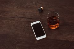Glass with whiskey, cork and mobile phone lie on a wooden table royalty free stock image
