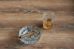 Glass of whiskey with cuban cigar on a brown wooden table. Top view. Royalty Free Stock Image