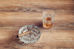 Glass of whiskey with cuban cigar on a brown wooden table. Top view. Stock Image