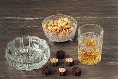 Glass of whiskey, a cuban cigar, nuts and chocolates on a grey wooden table. Close-up view. Stock Images
