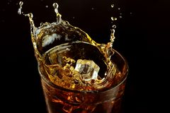 A glass of whiskey on a dark background. Splash ice cube. stock photos