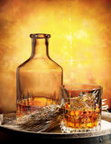 Glass of whiskey decanter and ears of wheat Royalty Free Stock Photos