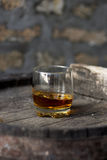 Glass of whiskey in distillery. Glass filled with whiskey, neat without ice, standing on a wooden barrel in distillery with barrels in the background stock image
