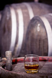 Glass of whiskey in distillery. Glass filled with whiskey, neat without ice, standing on a wooden barrel in distillery with barrels in the background royalty free stock photography