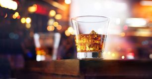 Glass of whiskey drink with ice cube on wooden table. Glass of whiskey drink with ice cube on table wooden bar, colorful night background Stock Image