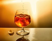 Glass of whiskey with drops and ice on an orange background stock photography