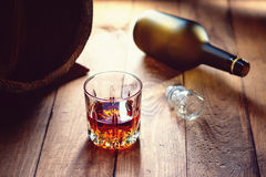 Glass of whiskey and empty bottle Stock Photos