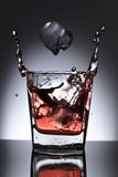 Glass of whiskey with falling ice on a black background Stock Images