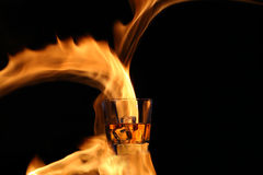 Glass with whiskey in the fire Royalty Free Stock Photo
